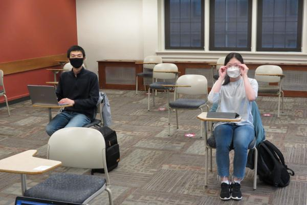 Two students, masked and distanced.