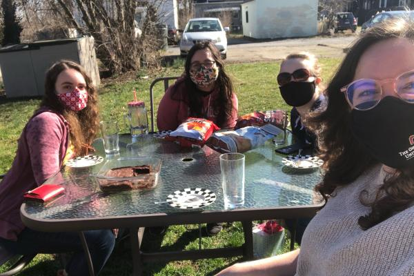 Members of an undergraduate mentoring group meeting masked and outdoors