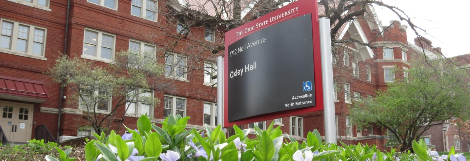 Oxley Hall sign, with building in background and spring flowers in foreground